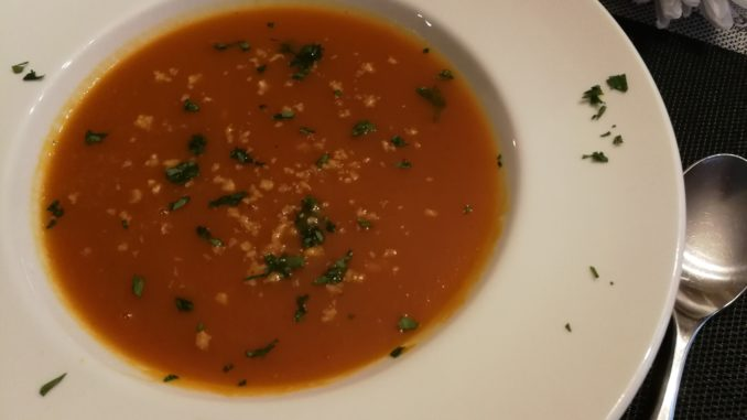 Soup garnished with walnuts and parsley