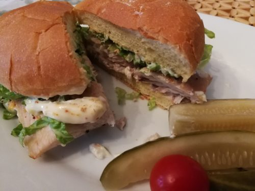 Spicy fish sandwich on a potato roll with dill pickles