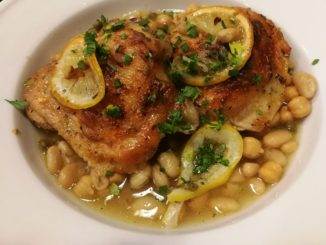 Two baked chicken thighs over white bean stew