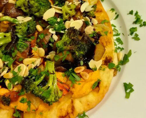 Roasted Vegetables top Roasted Red Pepper Hummus on a Naan Flatbread