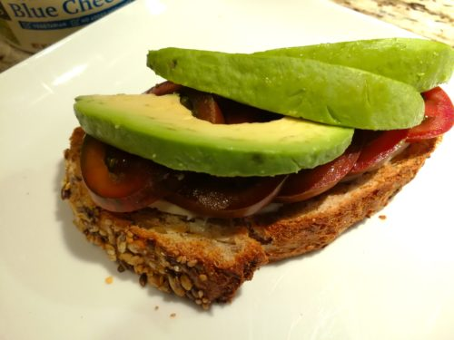 Spread toast with butter and add tomato and avocado slices