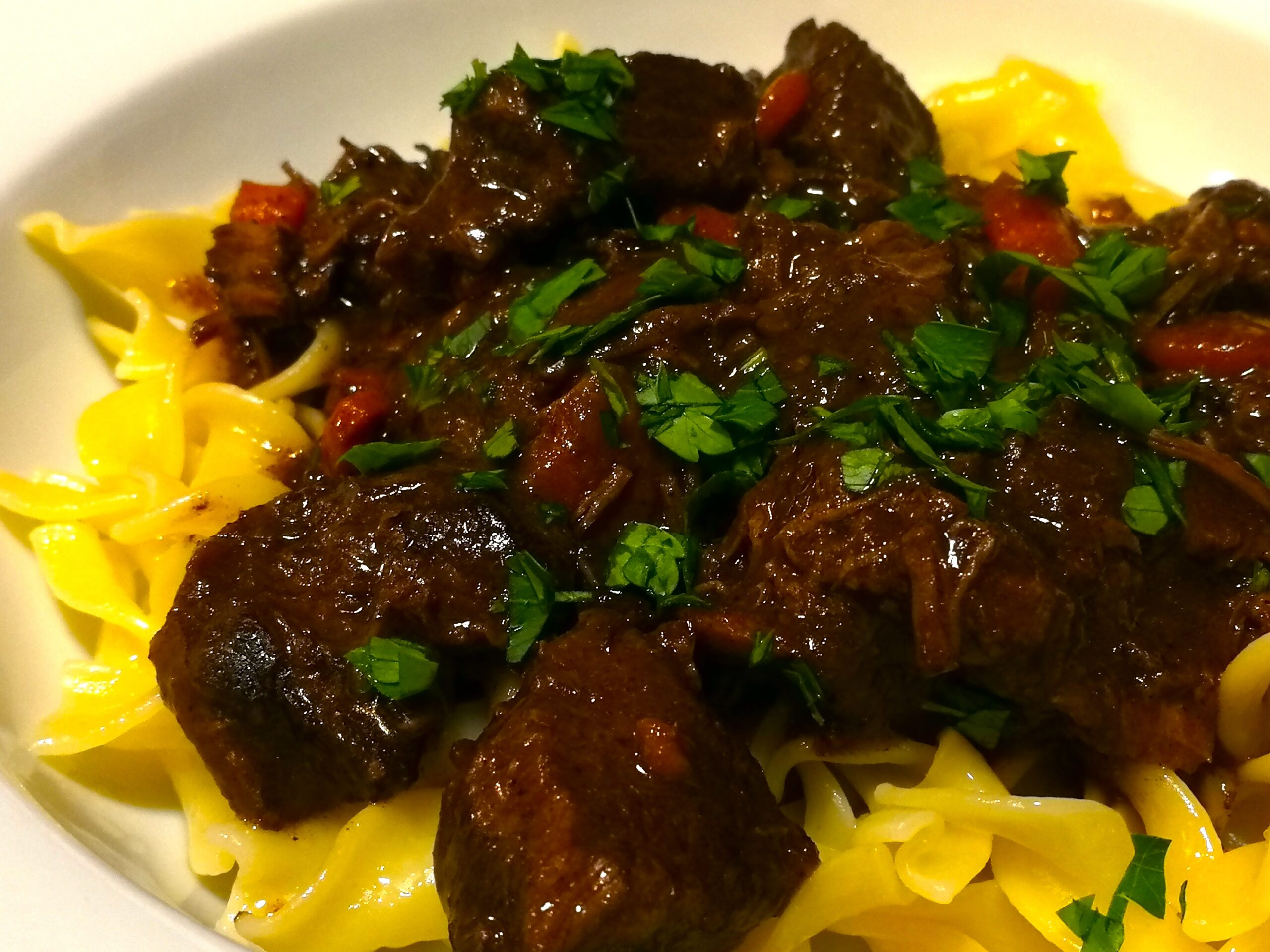 Beef Bourguignon served over buttered egg noodles