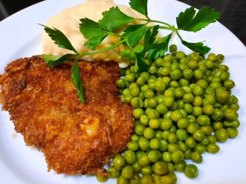 Crispy Pork Schnitzel served with mashed potatoes and peas