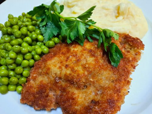 Crispy Pork Schnitzel served with peas and mashed potatoes