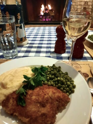 Crispy Pork Schnitzel, peas, mashed potatoes in front of the fireplace